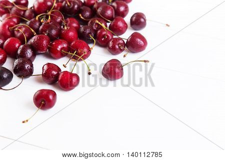 Ripe red cherries with water drops on a white background. Space for text