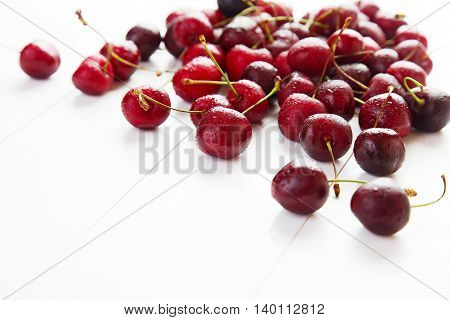 Red cherries with water drops on a white background. Space for text