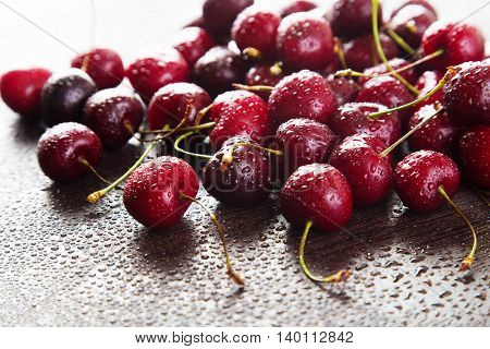 Ripe red cherries with water drops on a dark background. Space for text