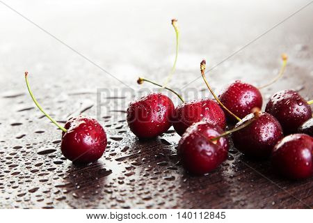 Ripe red cherries with water drops on a dark table. Space for text