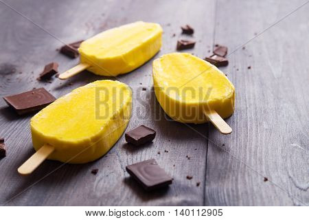 Yellow ice cream with chocolate bars on dark wooden table. Space for text.