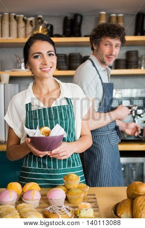 Portrait of waitress holding bowl with snack while waiter using coffee machine