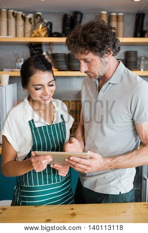 Waiter and waitress discussing over digital tablet in cafeteria