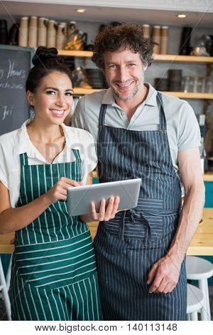 Portrait of waiter and waitress holding digital tablet in cafeteria