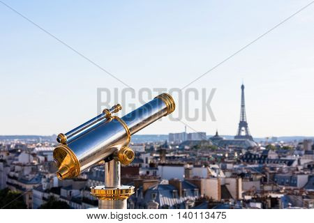 Touristic telescope overlooking Eiffel Tower from the roof of Printemps Department Store Paris France
