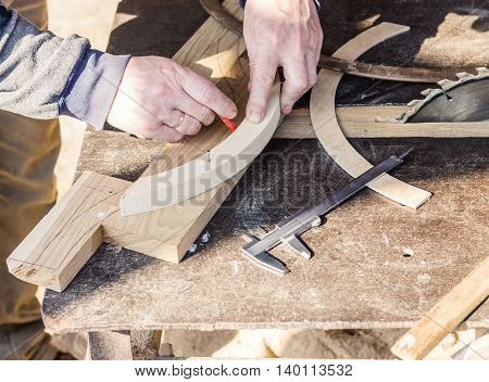 Carpenter is measuring wooden parts to make a furniture.