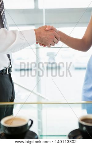 Mid section of businessman shaking hands with colleague in office