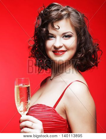 A beautiful happy woman in a red dress holding a glass of sparkling wine or Champagne.