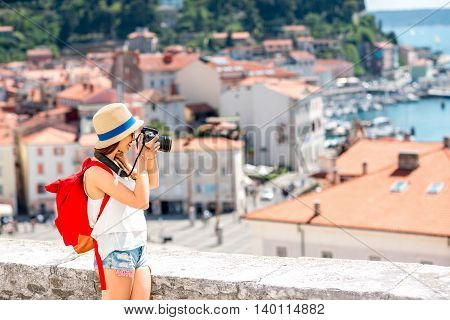 Young female traveler with red backpack photographing with photo camera Piran old town. Traveling in Slovenia