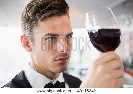 Close-up of waiter looking at a glass of wine in restaurant