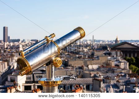 Touristic telescope overlooking Paris from the roof of Printemps Department Store