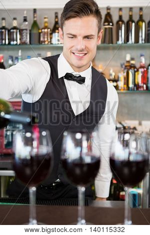 Waiter pouring wine into glasses in restaurant