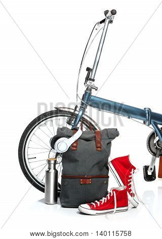 The new modern urban folding bike and suitcase, sneakers, thermos on white background. The travel, tourism and holidays concept