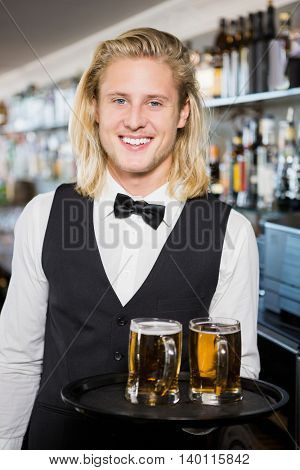 Portrait of waiter holding tray with beer mug in restaurant