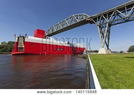 A huge car carrier passing the historic railway bridge crossing Kiel Canal at Hochdonn