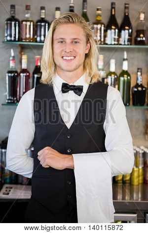 Portrait of waiter standing at bar counter in restaurant