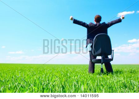Young businessman standing on green field near chair. Focus on grass