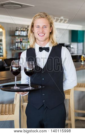 Portrait of waiter holding tray with glasses of red wine in restaurant