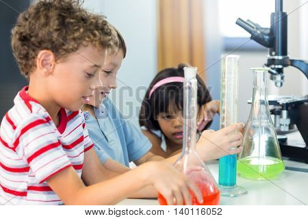 Schoolchildren with scientific equipment in laboratory