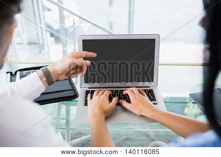 Businessman discussing with colleague over laptop in office