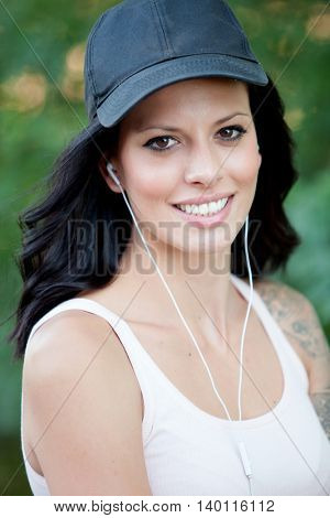 Cool woman with hat and headphones listening music walking in the forest
