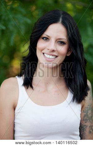 Beautiful brunette girl relaxing in the park wiht many plants of background