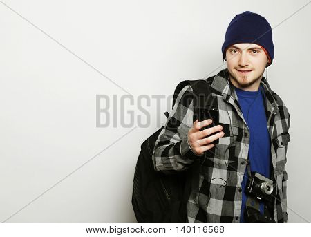 life style, education and people concept: young  man listening to music and using smartphone, while standing against grey background.