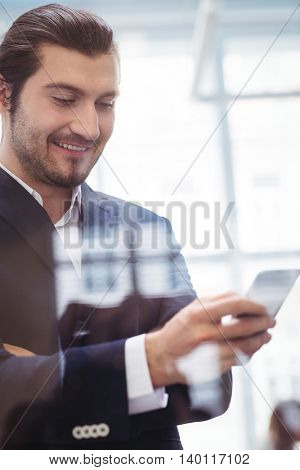 Smiling businessman using smart phone in meeting room at office seen through glass
