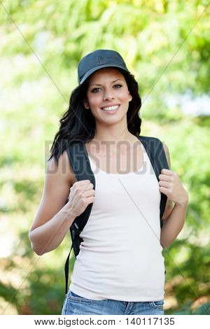 Beautiful brunette woman with cap and backpack hiking