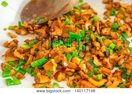 Sliced golden chanterelle fungus with chives frying on the pan