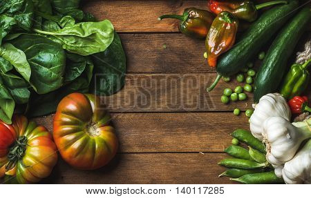 Fresh raw vegetable ingredients for healthy cooking or salad making on wooden background, top view, copy space. Diet or vegetarian food concept