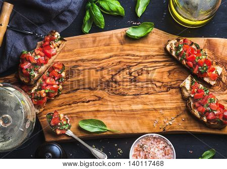 Tomato and basil bruschetta with glass of white wine on olive wooden board over black background, top view, copy space, horizontal composition