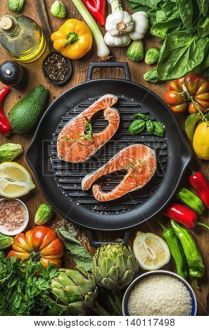 Dinner cooking ingredients. Raw uncooked salmon with vegetables, rice, herbs, lemon, artichokes, spices in iron grilling pan over wooden background, top view, vertical composition