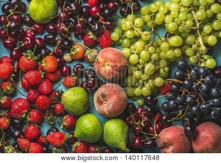 Healthy summer fruit variety. Black and green grapes, strawberries, figs, sweet cherries and peaches, top view, horizontal composition