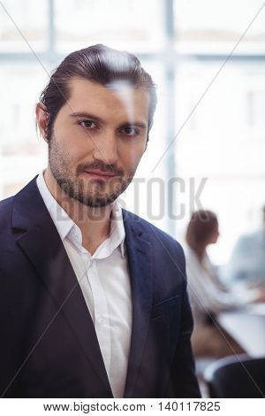 Portrait of confident businessman in meeting room at office seen through glass