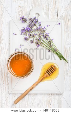Lavender honey in glass jar served with drizzlier and fresh lavender flowers on ceramic board over white painted wooden backdrop, top view