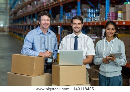 Worker team is posing and smiling to the camera in a warehouse
