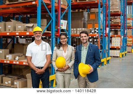 Portrait of managers are holding hard hat and posing in a warehouse