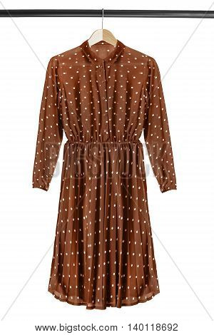 Brown chiffon dress on wooden clothes rack isolated over white