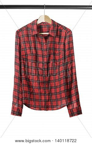 Red tartan shirt on wooden clothes rack isolated over white