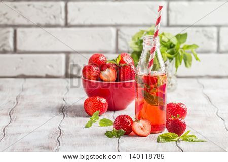 Refreshing summer drink with Strawberry in a glass bottle on white wooden table
