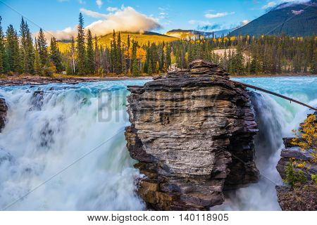 Powerful and scenic Athabasca Falls. Sunset illuminates the surrounding mountains. Canada, Jasper National Park