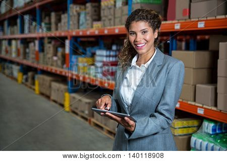 Business woman posing with her tablet in a warehouse