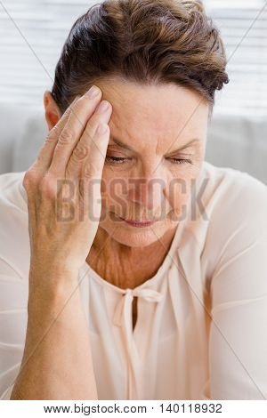 Upset woman suffering from headache while sitting at home