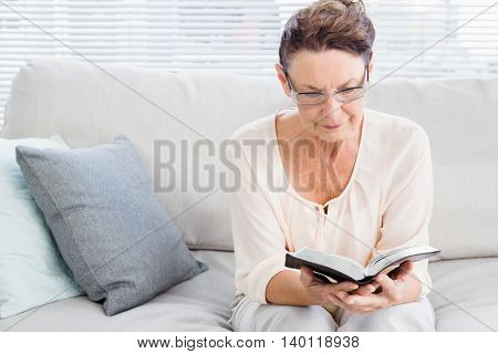Mature woman reading book while sitting on sofa at home