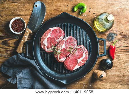 Ingredients for cooking Rib eye roast beef steak on black iron grilling pan over wooden background, top view, horizontal composition
