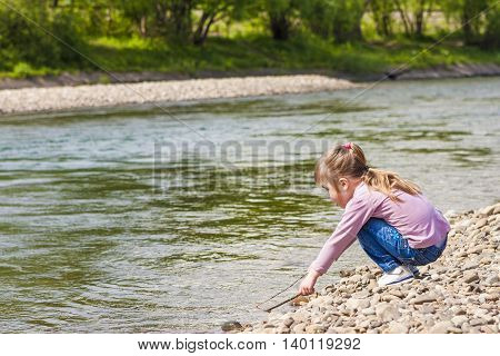Little girl playing near the river on a sunny day