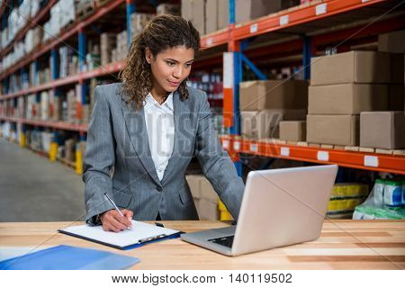 Business woman writing on her clipboard in a warehouse