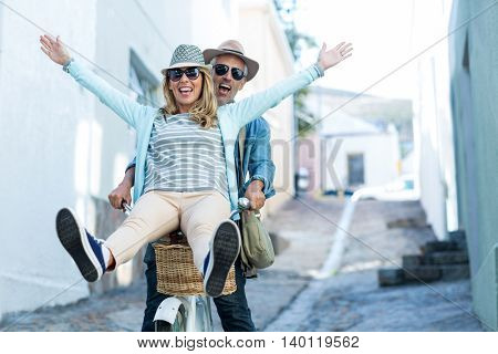 Mature couple enjoying while riding bicycle on street