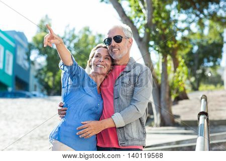 Mature man with woman pointing while standing on footpath in city